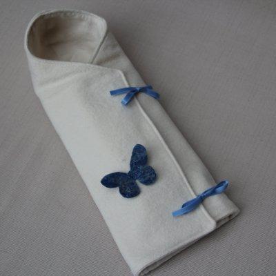 In de coocon zit een soort omslagdoekje van zachte flanel, afgewerkt met  een gevilte vlinder en strikjes van satijnband.